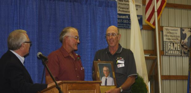 Fair Board President Dan Deml presented Howard Schoenfeld with the plaque signifying his induction into the Steele County Livestock Hall of Fame.