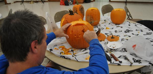 """Gary Jones works on a """"Hello Kitty"""" jack-o-lantern for his daughters during the pumpkin carving event."""