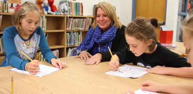"""One of Michelle Krell's trademarks as principal at Kasson-Mantorville Elementary is visiting every classroom and saying """"Good morning"""" to all students and staff members each morning. Krell is pictured with two of the 810 students at K-M, Tayler Lamphere, left, and Laney Bungum, right."""