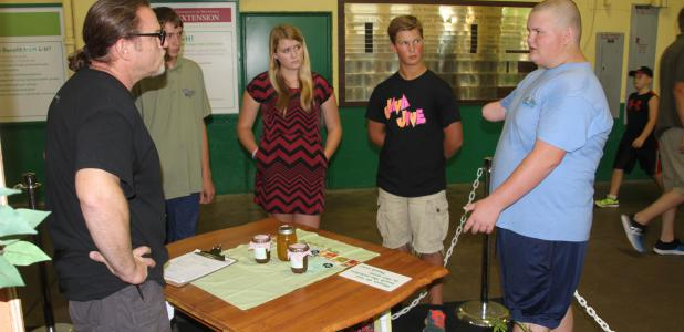 Craig Aarsvold, 13, of Dodge Center, right, explains his refinished table to a judge on the far left during 4-H conference judging at the Minnesota State Fair Friday afternoon. There were other 4-H'ers from around the state listening in during the judging session. Aarsvold won a trip in the shop project and earned a red ribbon.