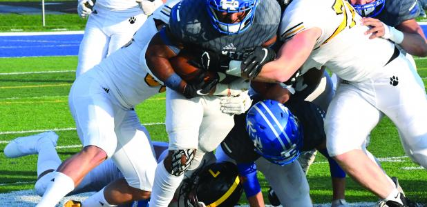 K-M Running Back Anthony Moe-Tucker fights off the defensive line of the Mankato East team.