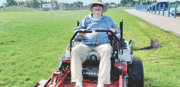 As a member of the KM Lions mowing crew, Terry Meyer helps out by mowing the grass to help the schools maintenance crew.