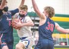 Ethan Slaathaug hangs on to the basketball during Hayfield's Class A quarterfinal game against Legacy Christian Academy.