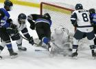 Brody Lamb (No.7) crashes the net against Century High at Graham Arena in Rochester as Matt Donnovan (No.14) and Gavin Giesler (No. 15) play defense. The Wildcats defeated Century 4-2 March 11.